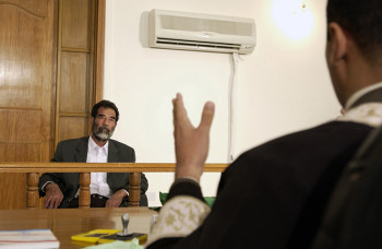 Former and deposed President of Iraq, Saddam Hussein, sits before an Iraqi judge at a courthouse in Baghdad, Iraq, where he has his initial interview to inform him of what he is being investigated for and his legal rights read to him.
